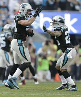 Carolina Panthers' Luke Kuechly, left, celebrates with Bene' Benwikere, right, after his interception against the Atlanta Falcons in the second half of an NFL football game in Charlotte, N.C., Sunday, Dec. 13, 2015. (AP Photo/Bob Leverone)