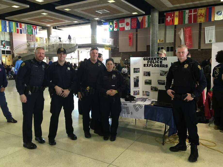 Greenwich police officers set up a booth at the student center at Greenwich High School on Thursday to answer questions about the Explorer program, a law-enforcement education program. Photo: /sent In Photo / Greenwich Explorers