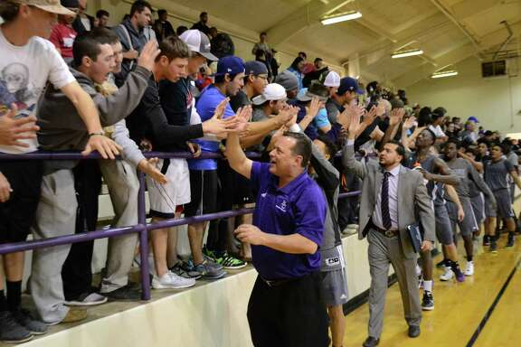 Ranger College head coach Billy Clyde Gillispie high-fives students in the bleachers at the Ron Butler Gym on Jan. 23, 2016, following the Rangers' 127-50 non-conference victory over the Metroplex Lightning.