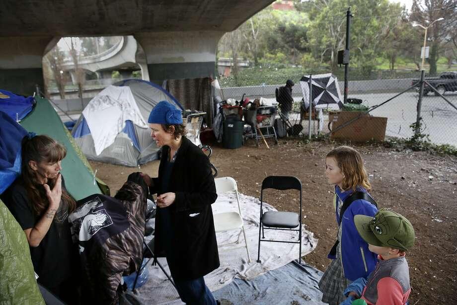 Christine Boyer (left) gets a blanket-jacket from Kim Frazar Blantz at a Highway 101 encampment. Photo: Lea Suzuki, The Chronicle