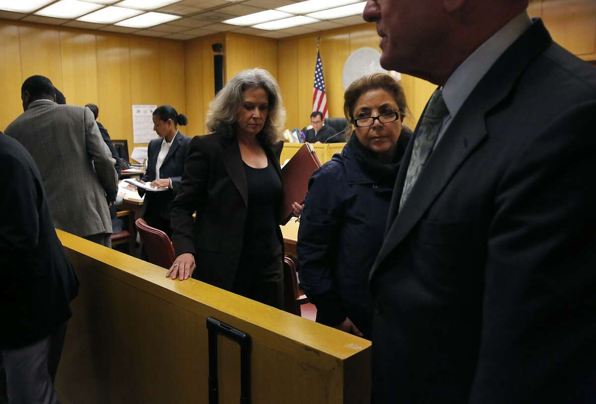 Nazly Mohajer, right center, walks back from appearing in front of a judge with Keith Jackson and Zula Jones Jan. 29, 2016 for an appearance in Superior Court for charges of accepting bribes for political favors in the Hall of Justice Building in San Francisco, Calif.