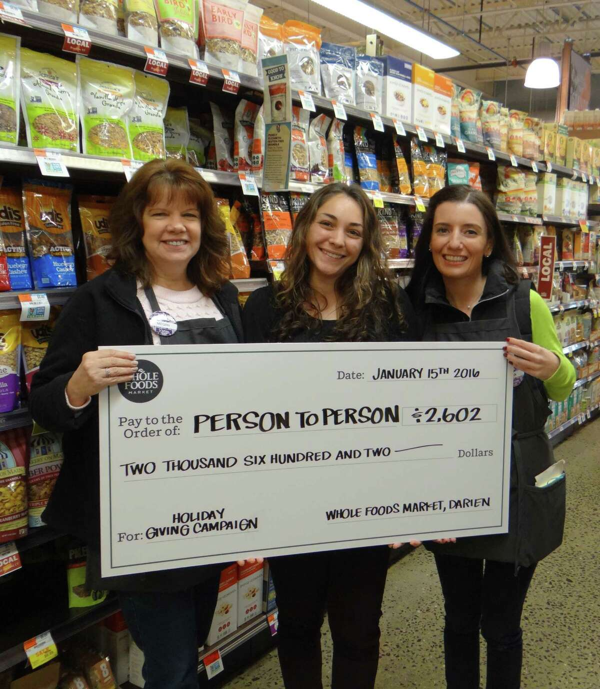 Person-to-Person Darien Site Manager Sophie Neumann (middle) accepts $2,602 check from Whole Foods Market Store Team Leader Megan Neisser (left) and Marketing Team Leader Lucia Albero (right), at Whole Foods Darien's Holiday Giving Campaign.
