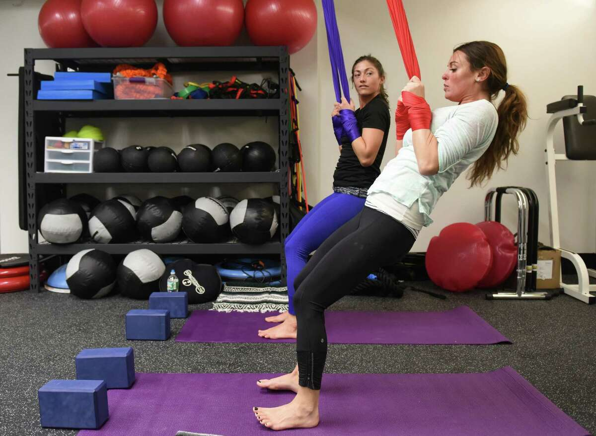 Yoga/fitness training coach Nichele Allen, left, guides Norwalk resident Staci Thomas through a workout at Mason Street Strength and Fitness in Greenwich.