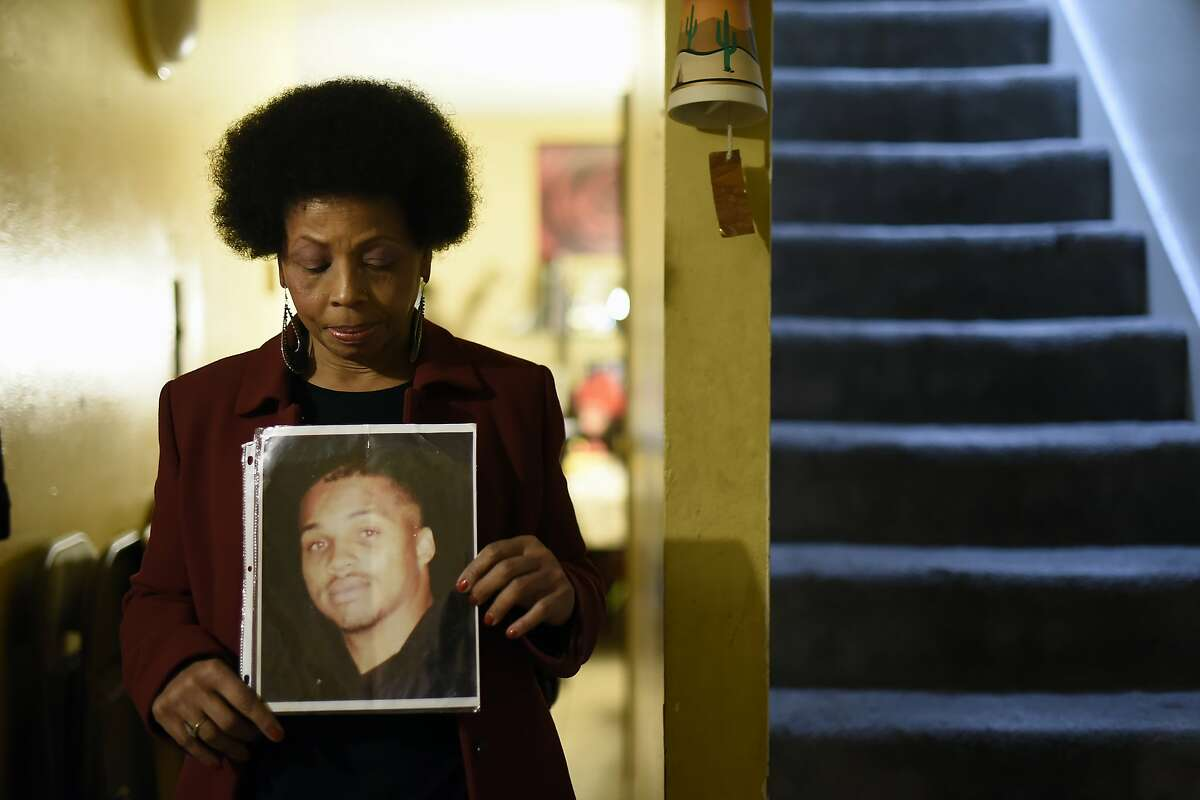 Mattie Scott poses for a portrait with a picture of her murdered son George Scott at her apartment in the Western Addition neighborhood of San Francisco, CA Wednesday, December 23, 2015. Mattie's son George Scott was 24 years old in 1996 when he was shot multiple times while trying to deescalate an argument between attendees of a college graduation party in the Western Addition, one of many unsolved murders in the predominately African-American neighborhood.