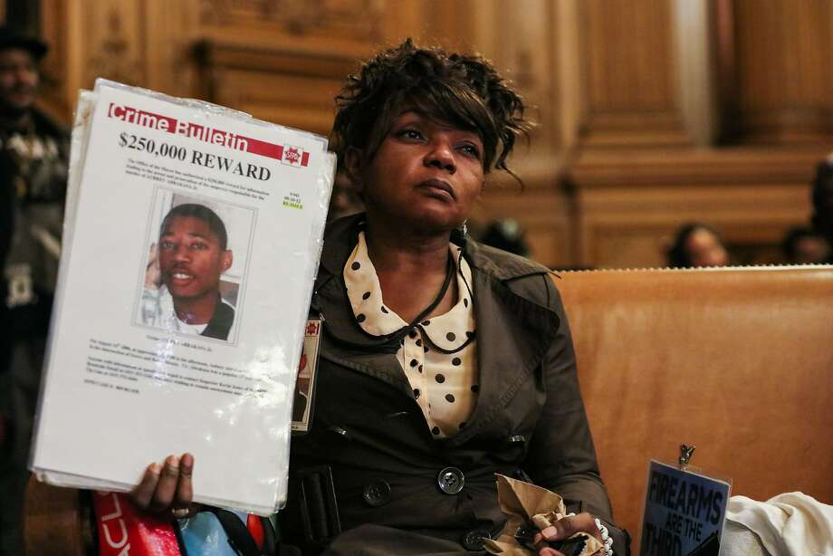 """Paulette Brown holds a sign reading """"Crime Bulletin"""" with the face of her son on it at City Hall in San Francisco, California on Tuesday, January 12, 2016. Paulette Brown lost her son her 17-year-old son Aubrey Abrakasa to gun violence nine years ago and is still waiting for investigators to make an arrest. Photo: Gabrielle Lurie, Special To The Chronicle"""