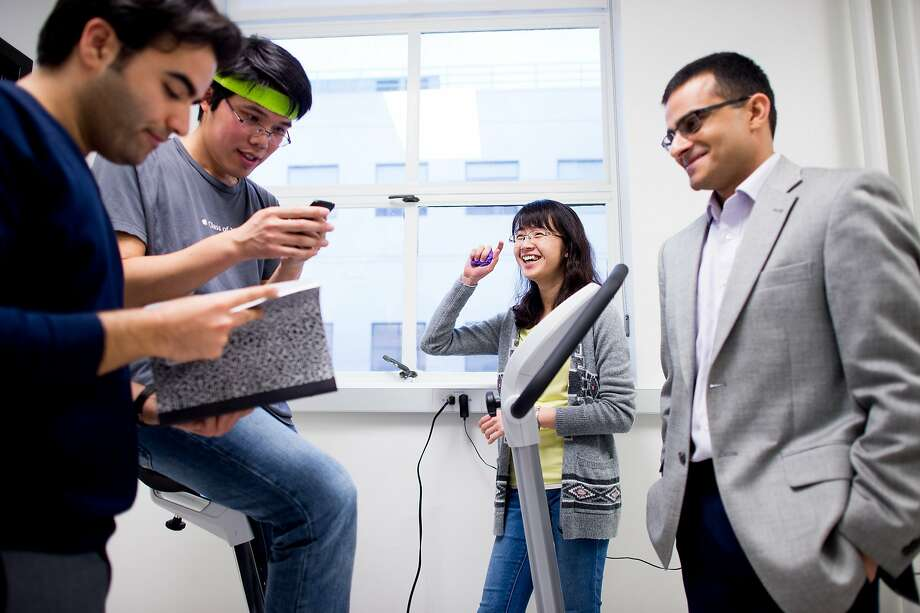 UC Berkeley Professor Ali Javey, right, works with researchers in his lab on Friday, Jan. 29, 2016, in Berkeley. From left to right are Javey, Hnin Yin Yin Nyein, Wei Gao and Sam Emaminejad. Photo: NOAH BERGER / SAN FRANCISCO CHRO