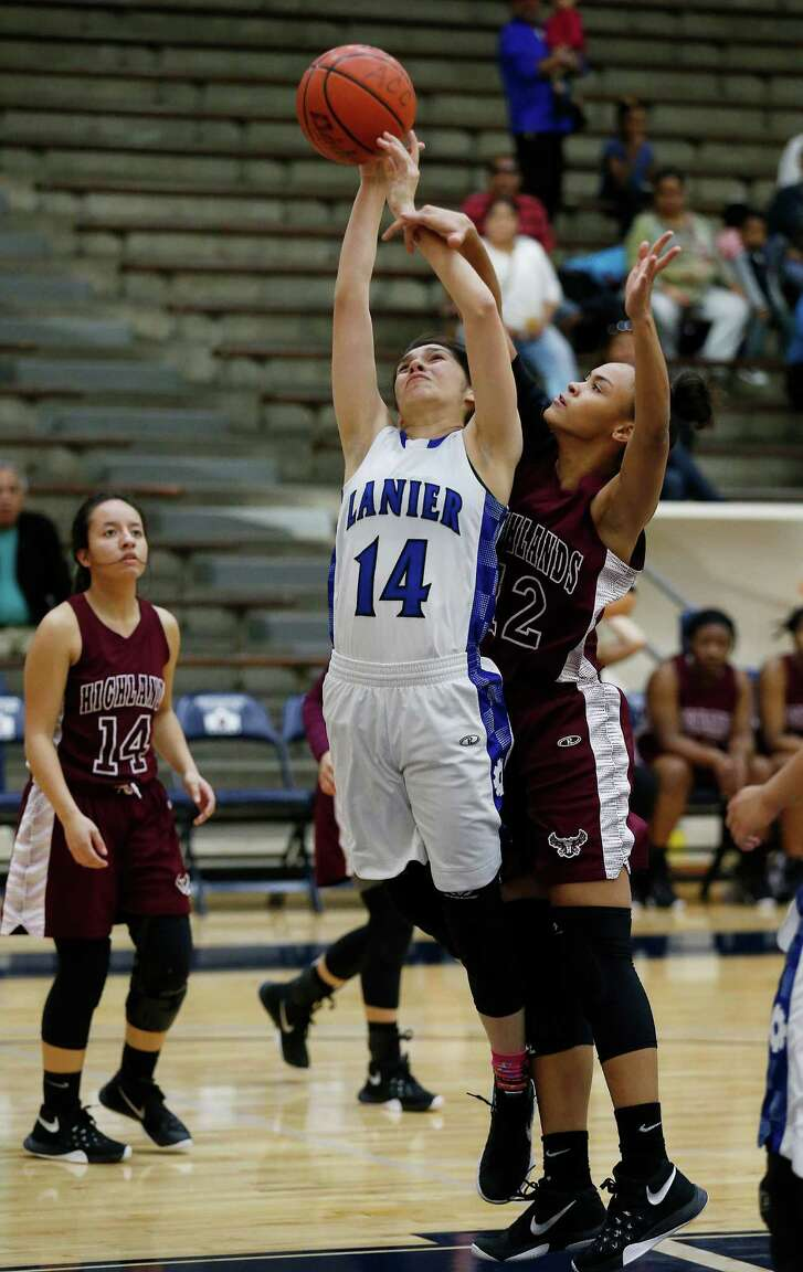 Lanier's Ruby Garza (14) gets fouled while attempting a shot by Highlands' Aaliyah Prince (22) in girls basketball at the Alamo Convocation Center on Friday, Jan. 29, 2016. Lanier rallied to defeat Highlands, 66-62. (Kin Man Hui/San Antonio Express-News)