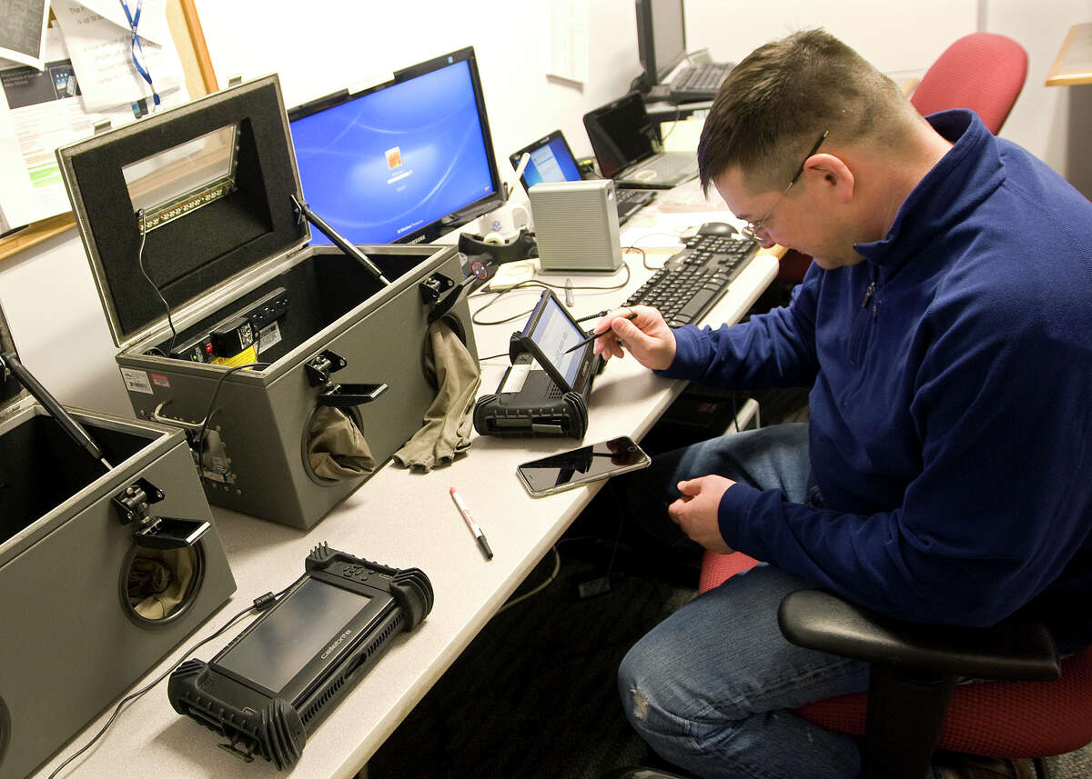 """In this Feb. 13, 2015 photo Mark Newth, a forensic science examiner, taps on an electronic device used to extract data from cell phones at the Connecticut State Police Forensic Science Laboratory in Meriden, Conn. A UTSA professor urges information security efforts take in the """"human element"""" behind cyber attacks."""