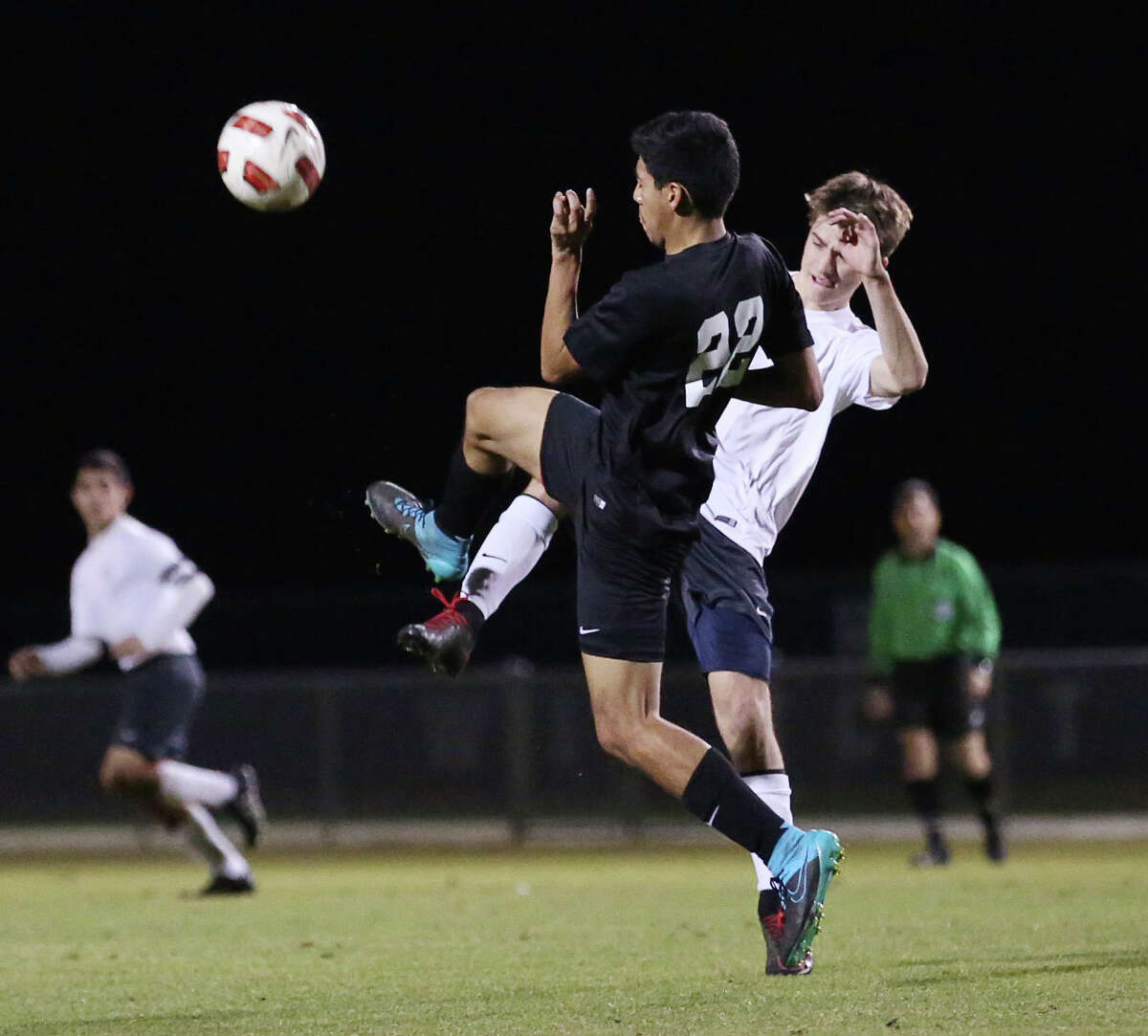 Spring Woods defender Cesar Escalante (22) goes for the ball against Tomball Memorial midfielder Ethan Wade (16) during the first half of a soccer game between Spring Woods and Tomball Memorial Friday, Jan. 29, 2016, in Tomball.