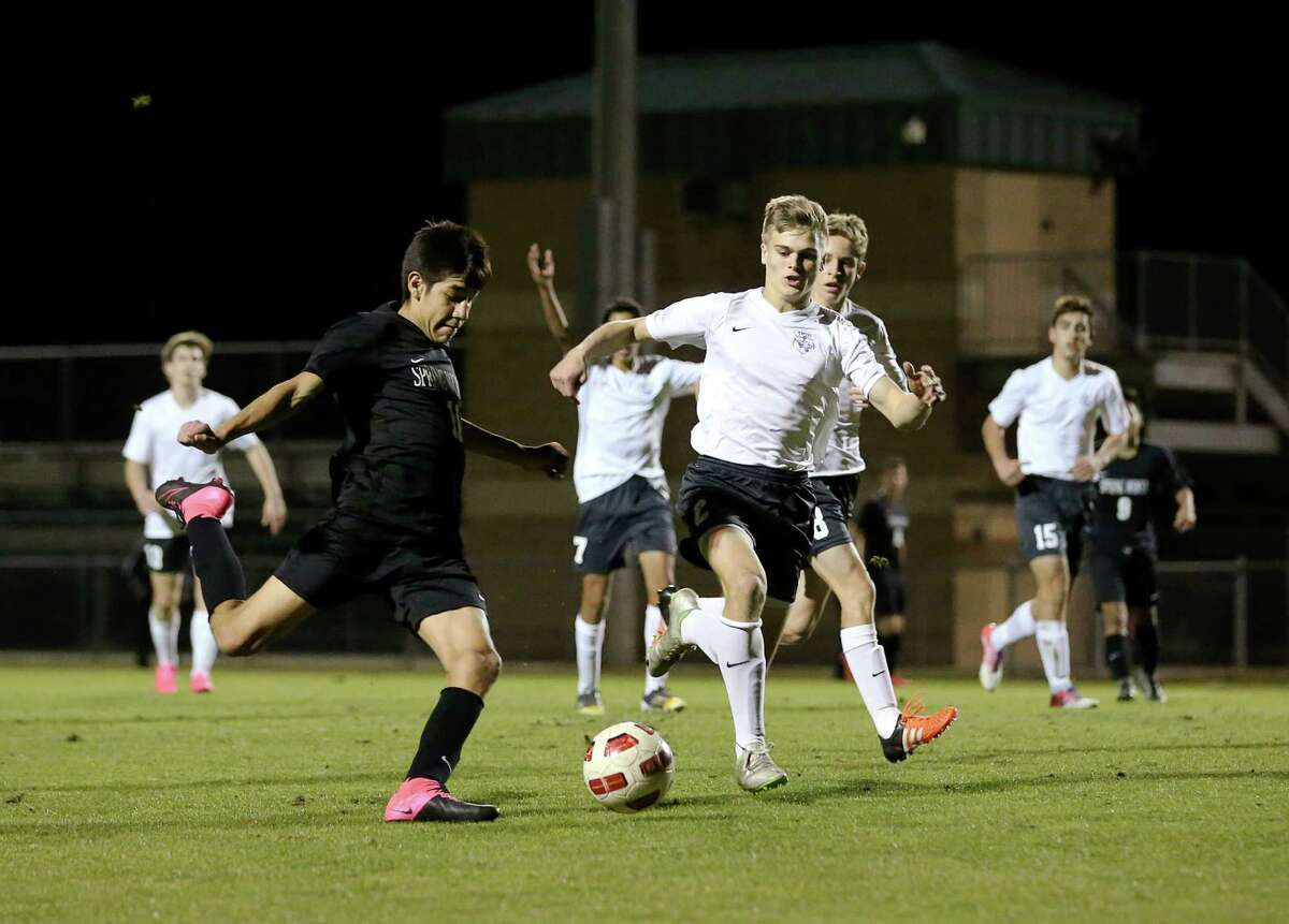 Spring Woods forward Jose Gonzalez (11) shoots past Tomball Memorial midfielder Gage Beaty (2) during the first half of a soccer game between Spring Woods and Tomball Memorial Friday, Jan. 29, 2016, in Tomball.