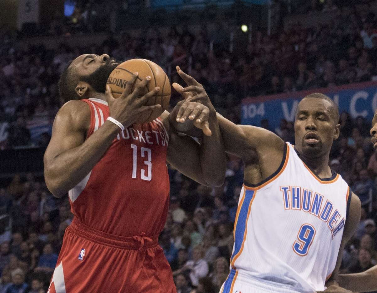 OKLAHOMA CITY, OK - JANUARY 29 : Serge Ibaka #9 of the Oklahoma City Thunder blocks James Harden #13 of the Houston Rockets as he drives to the basket during the first quarter of a NBA game at the Chesapeake Energy Arena on January 29, 2016 in Oklahoma City, Oklahoma. NOTE TO USER: User expressly acknowledges and agrees that, by downloading and or using this photograph, User is consenting to the terms and conditions of the Getty Images License Agreement. (Photo by J Pat Carter/Getty Images)