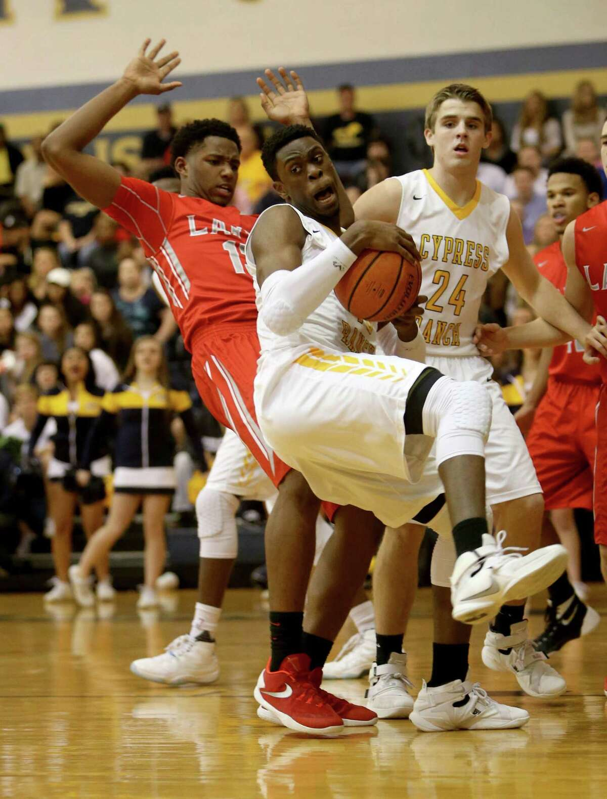 Anthony Agu (40), of Cypress Ranch, grabs a rebound in front of Jared Garcia (13), of Cypress Lakes, during the first quarter at Cypress Ranch High Friday, Jan. 29, 2016, in Cypress, Texas.
