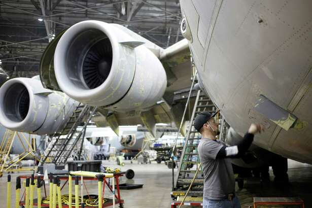 A maintenance technician inspects a U.S Air Force Boeing C-17 Globemaster III airplane at the Boeing Co. Global Services and Support facility in San Antonio, Texas, on Thursday. Government figures Friday are forecast to show GDP growth decelerated in the final three months of 2015, with a sharp slackening in inventories by manufacturers and other businesses and a larger trade deficit behind the slowdown. Must credit: Bloomberg photo by Luke Sharrett.