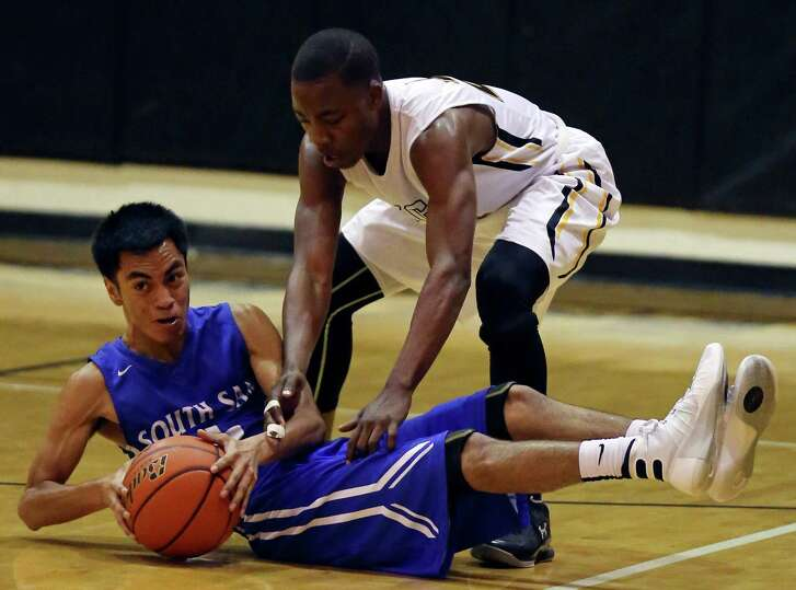 South San's Adrian Garcia and East Central's Kvon Rice grab for a loose ball during first half action Friday Jan. 29, 2016 at the Stan Bonewitz Center on the East Central High School campus.
