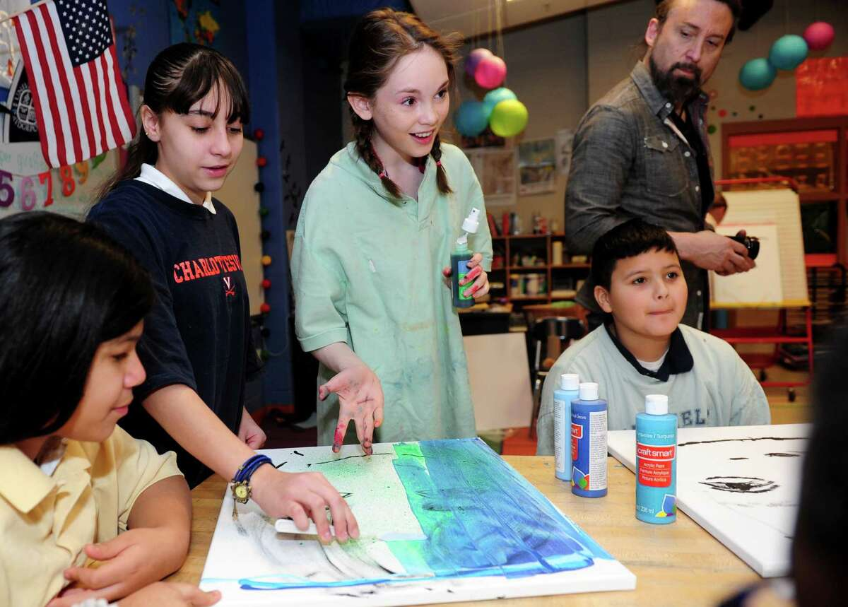 Artist Autumn de Forest, a 14-year-old painting prodigy, shows Aiyannah Estramera, standing at left, a way to add color to her self-portrait during a visit to Bridgeport's Barnum Elementary School on Friday.