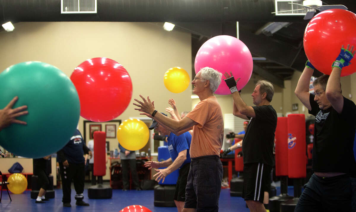 Mike Williamson, 68, center, throws a ball to his wife, Julie Williamson, 65, not pictured, during a boxing class for people with Parkinson's disease at Battenberg's Blackbelt Academy, Inc, Thursday, Jan. 21, 2016, in Kingwood. Mike doesn't have Parkinson's. He comes to support his wife who has had it for about two and a half years.