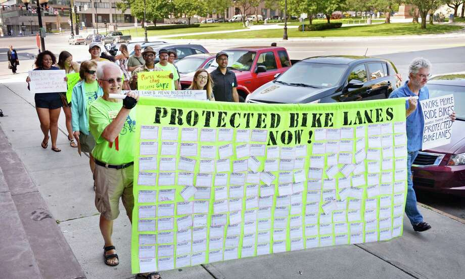 Albany's Protected Bicycle Lane Coalition delivers a banner with postcards they have collected from Albany residents and visitors who want a protected bicycle lane for Madison Avenue to City Hall Friday August 14, 2015 in Albany, NY.  (John Carl D'Annibale / Times Union) Photo: John Carl D'Annibale / 00033001A