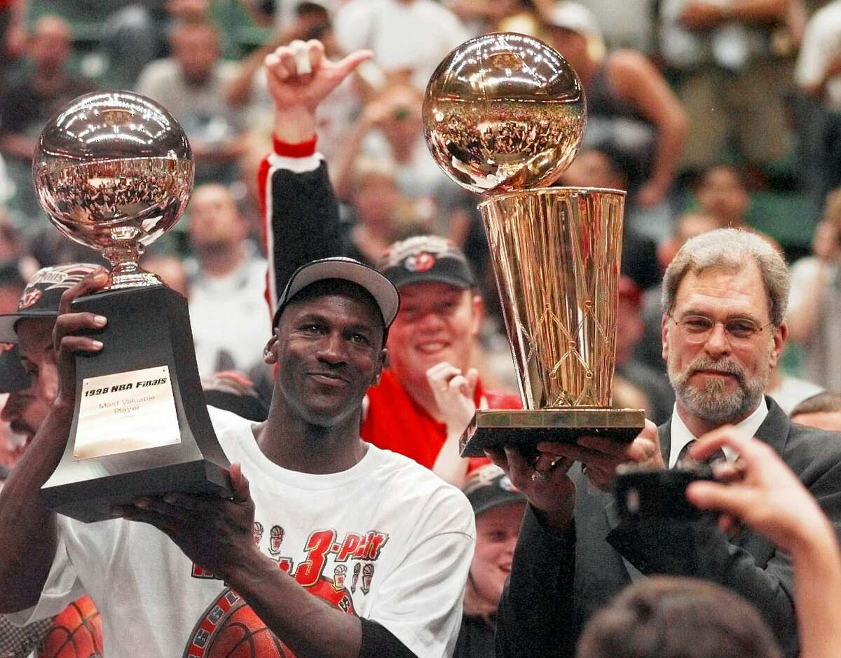 Chicago Bulls' Michael Jordan, left, holds the Most Valuable Player trophy as coach Phil Jackson holds the NBA Championship trophy after the Bulls defeated the Utah Jazz 87-86 in Game 6 of the NBA Finals in Salt Lake City, Sunday, June 14, 1998.