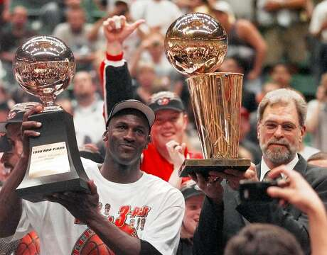 Chicago Bulls' Michael Jordan, left, holds the Most Valuable Player trophy as coach Phil Jackson holds the NBA Championship trophy after the Bulls defeated the Utah Jazz 87-86 in Game 6 of the NBA Finals in Salt Lake City, Sunday, June 14, 1998. Jackson won't return to the Bulls, despite an offer from chairman Jerry Reinsdorf to coach for another year, Jackson's attorney, Todd Musberger, confirmed Sunday night, June 21, 1998.
