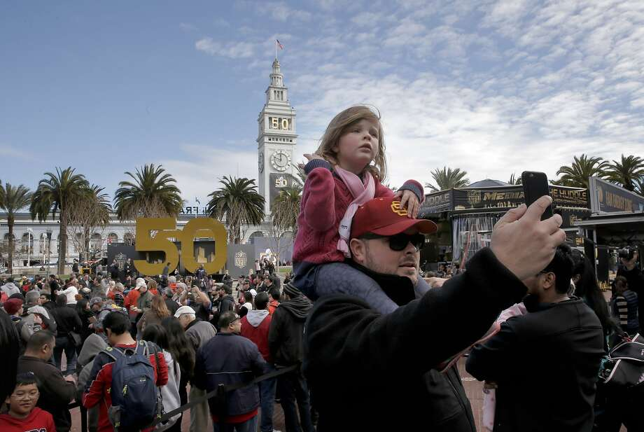 Clay Marquez and his daughter Penny, 3 of San Francisco join the huge crowds at Super Bowl City on opening day. Photo: Michael Macor, The Chronicle