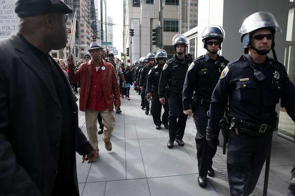 Police officers escort demonstrators with the Justice for Mario Woods Coalition on a march past the site of Super Bowl City in San Francisco, Calif. on Saturday, Jan. 30, 2016.