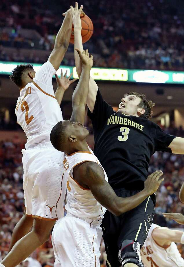 Demarcus Holland gets the ball as he and Kendal Yancy block up Commodores center Luke Kornet at the basket as Texas hosts Vanderbilt at the Erwin Center in Austin on January 30, 2016. Photo: TOM REEL, STAFF / SAN ANTONIO EXPRESS-NEWS / 2016 SAN ANTONIO EXPRESS-NEWS
