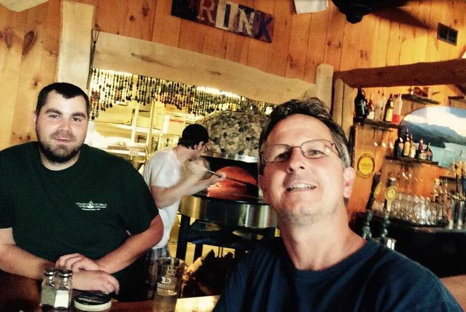Steve Holmes, right, owner of Sticks & Stones Wood Fired Bistro & Bar in Schroon Lake, with bartender Colin Davidson in front of the restaurant's wood fired oven. Holmes said raising the minimum wage has a ripple effect that the government doesn't always consider. Photo: Rulison, Larry