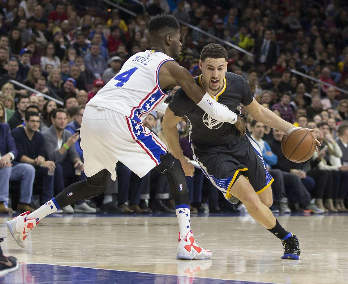 PHILADELPHIA, PA - JANUARY 30: Klay Thompson #11 of the Golden State Warriors drives around Nerlens Noel #4 of the Philadelphia 76ers on January 30, 2016 at the Wells Fargo Center in Philadelphia, Pennsylvania. NOTE TO USER: User expressly acknowledges and agrees that, by downloading and or using this photograph, User is consenting to the terms and conditions of the Getty Images License Agreement. (Photo by Mitchell Leff/Getty Images)