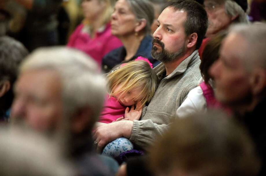 Scott Carlone of Hoosick Falls, center, and his daughter Sadie Carlone, 5, attend a community meeting addressing the PFOA groundwater contamination in the village and wells in the Town of Hoosick on Saturday, Jan. 30, 2016, at Bennington College in Bennington, Vt. (Cindy Schultz / Times Union) Photo: Cindy Schultz / Albany Times Union