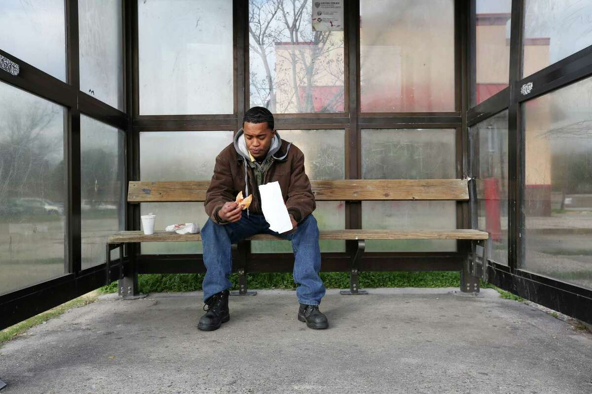 Da'Jon Gradney eats a fresh donut as he waits for the first of two buses and a train he rides on his way home from his monthly meeting with his probation officer Friday, Jan. 22, 2016, in Houston. Gradney left his apartment before 6 a.m. and rode three buses to make it to the 8 a.m. appointment.