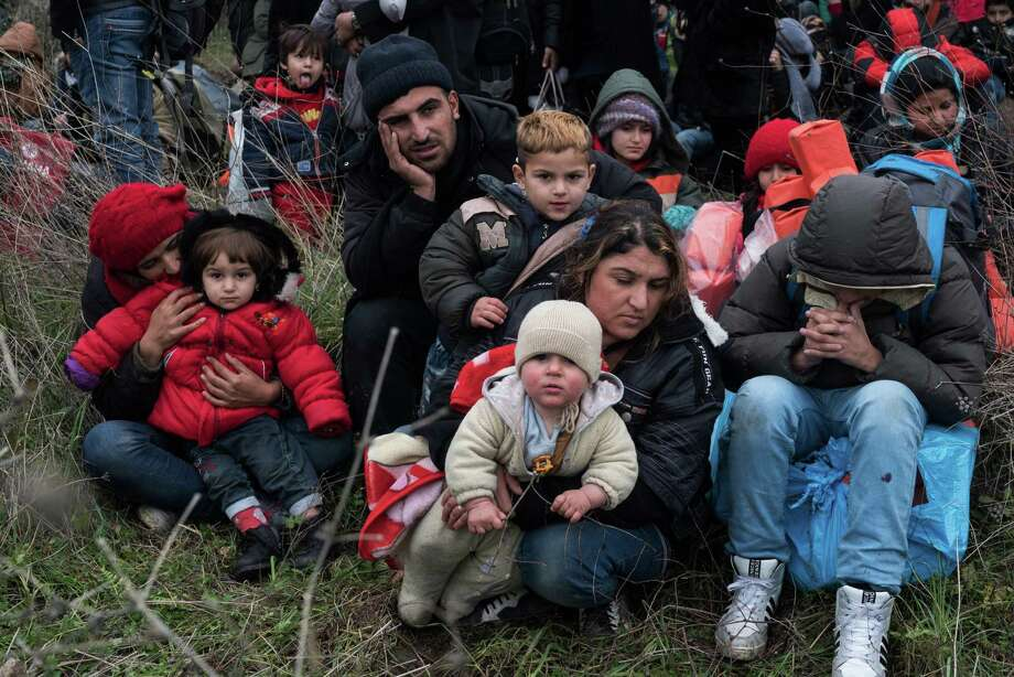Migrants wait to travel to the Greek island of Lesbos, near the Aegean town of Ayvacik, Turkey, Friday, Jan. 29, 2016. Italian Premier Matteo Renzi said in Berlin on Friday that he is expecting an answer soon from the European Commission on his country's questions about providing 3 billion euros in aid to Turkey to help with Syrian refugees.(AP Photo/Halit Onur Sandal) ORG XMIT: ANK110 Photo: Halit Onur Sandal / AP