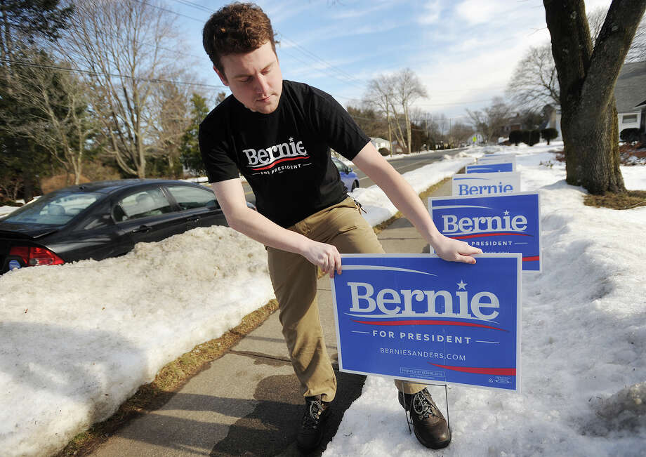 Nick Smith, 27, a property manager, places a Bernie Sanders for President lawn sign in front of his home on New Haven Avenue in Milford on Wednesday. He plans to travel to New Hampshire to support the Sanders campaign as the New Hampshire primary approaches. Photo: Brian A. Pounds / Hearst Connecticut Media / Connecticut Post