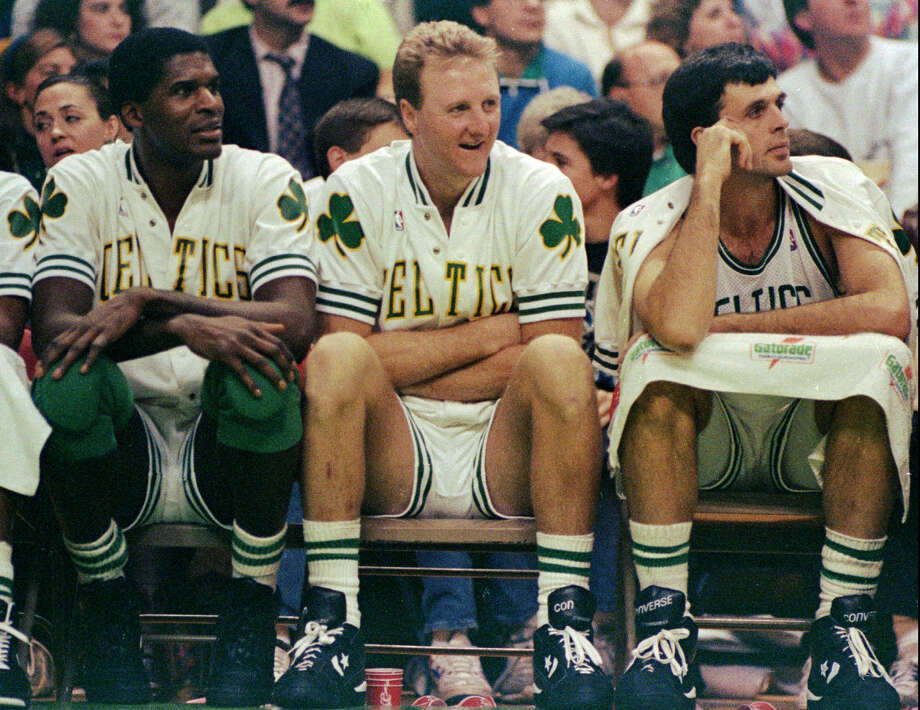 Boston Celtics stars (from left) Robert Parish, Larry Bird, and Kevin McHale watch their team win over the Washington Bullets at the Boston Garden on Nov. 30, 1991. Photo: Stephan Savoia /Associated Press / AP