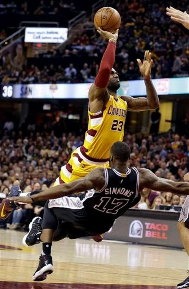 Cleveland Cavaliers' LeBron James (23) is fouled by San Antonio Spurs' Jonathon Simmons (17) in the first half of an NBA basketball game Saturday, Jan. 30, 2016, in Cleveland. (AP Photo/Tony Dejak) Photo: Tony Dejak, Associated Press
