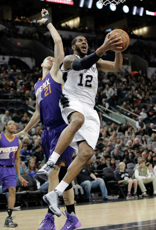 Spurs forward LaMarcus Aldridge drives around Phoenix Suns center Alex Len during the first half on Dec. 30, 2015, in San Antonio. Photo: Eric Gay /Associated Press / AP