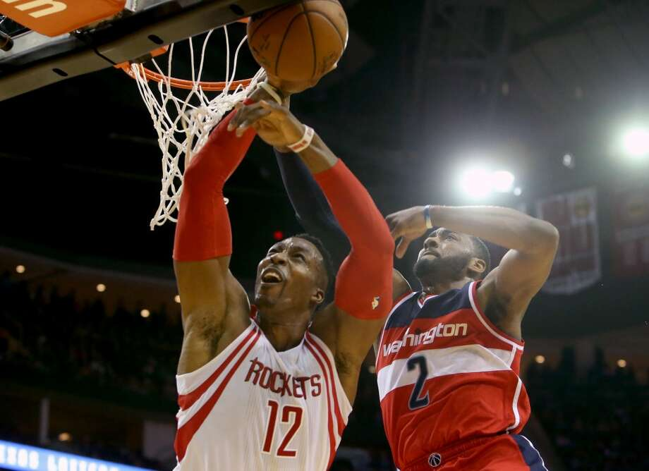 John Wall (right) fouls Dwight Howard in 2016, when Howard was a member of the Houston Rockets. The two are now teammates. Photo: Gary Coronado, Houston Chronicle