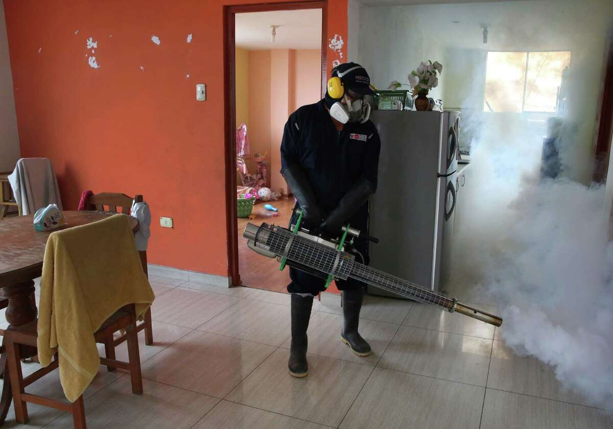 A health worker fumigates against the Aedes aegypti mosquito, a vector of the Dengue, Chikunguya and Zika viruses, inside a house in Lima, Peru, Friday, Jan. 29, 2016. The Zika virus causes only a mild illness in most people. But there's mounting evidence linking it to a birth defect, especially in Brazil.