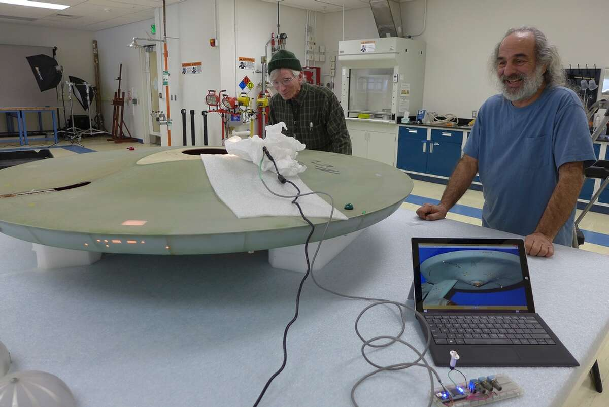 Museum specialists Zabih Sadighian (right) and Larry Berger do the first tests of LED lighting strips hidden inside the model.