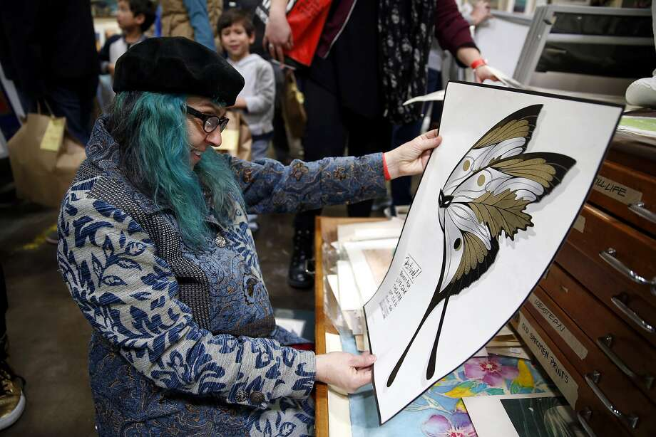 Jennifer Una examines a poster at the Oakland Museum's 57th annual White Elephant sale in Oakland, California, on Sunday, Jan. 31, 2016. Photo: Connor Radnovich, The Chronicle