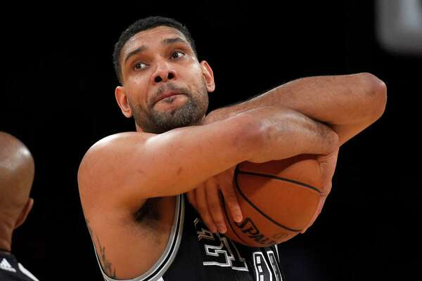 San Antonio Spurs center Tim Duncan hugs the ball prior to the Spurs' NBA basketball game against the Los Angeles Lakers, Friday, Jan. 22, 2016, in Los Angeles. (AP Photo/Mark J. Terrill)