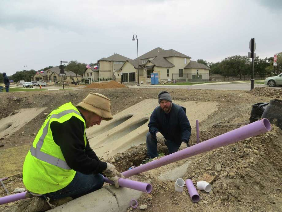 "Purple pipes being installed by Ricky Kellum (left) and Rudy Sanchez in the Esperanza development just east of Boerne will make possible the city's first delivery of ""reclaimed"" treated wastewater for irrigation in the subdivision in Kendall County. So far,  only model homes (rear) have been built in the huge development taking shape off Texas 46. Photo: Zeke MacCormack / Zeke MacCormack"