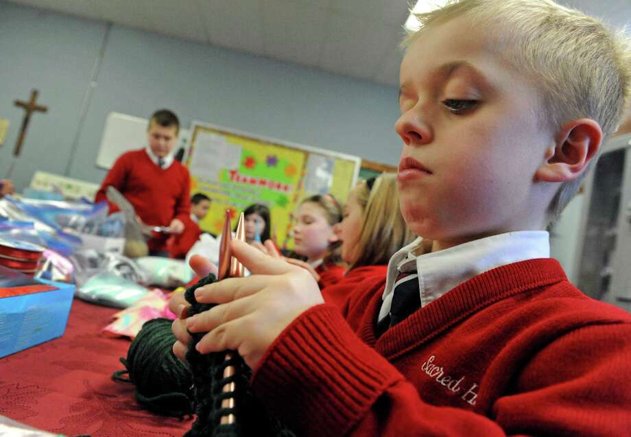 Fifth-grade student Seamus Camenga knits with classmates as they make gloves, hats and scarfs for the homeless at Sacred Heart School on Wednesday Jan. 27, 2016 in Troy, N.Y. (Michael P. Farrell/Times Union) Photo: Michael P. Farrell / 10035171A