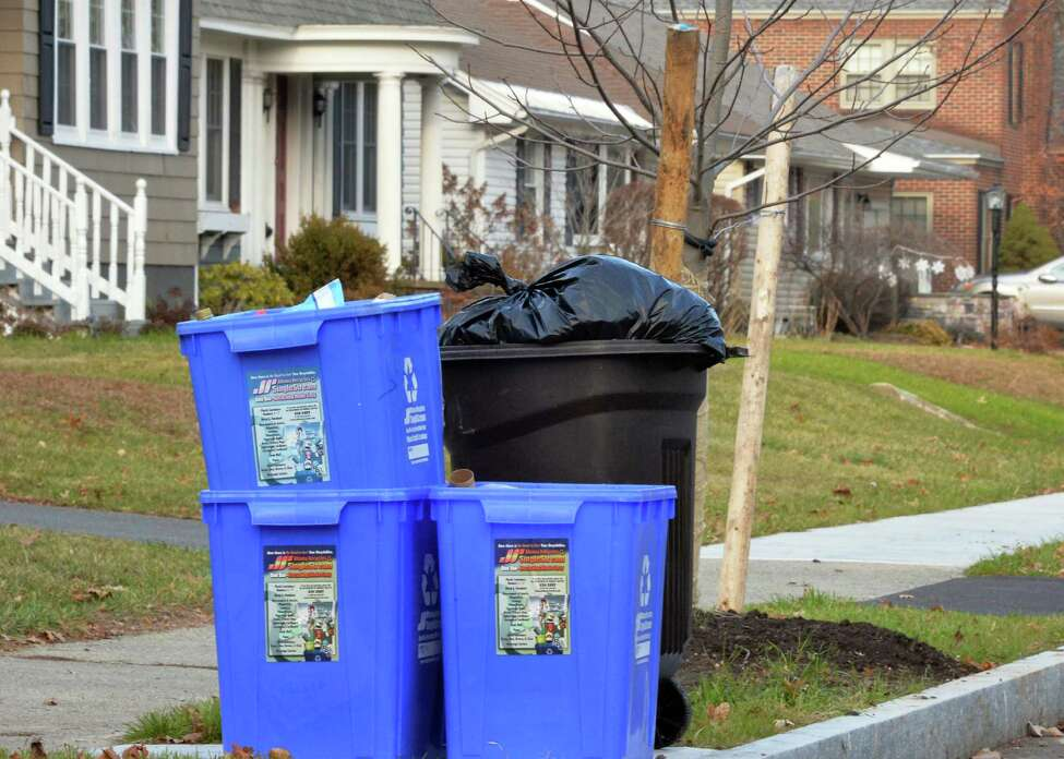 John Carl D?Annibale / Times Union Trash along Euclid Avenue awaits pickup by Albany city crews. City officials are considering a change to a ?pay as you throw? system that would charge Albany residents based on how much household trash they generate. Three blue containers are marked for recyclables.