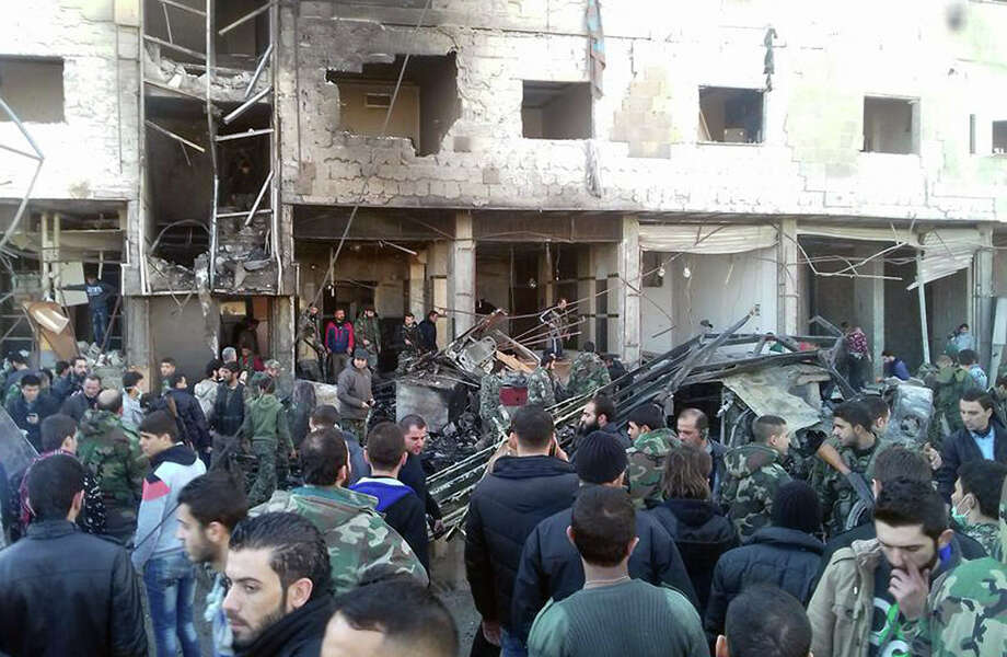 In this photo released by the Syrian official news agency SANA, Syrians gather where three bombs exploded in Sayyda Zeinab, a predominantly Shiite Muslim suburb of the Syrian capital, Syria, Sunday, Jan. 31, 2016. The triple bombing claimed by the extremist Islamic State group killed at least 45 people near the Syrian capital of Damascus on Sunday, overshadowing an already shaky start to what are meant to be indirect Syria peace talks. (SANA via AP) ORG XMIT: BEI105 Photo: Uncredited / SANA
