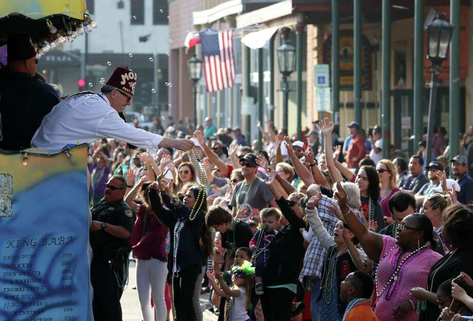 Richard Baker, second from left, leans out of a float to toss beads to onlookers during the Shriners Hospitals for Children-Galveston Parade along Strand Street Sunday, Jan. 31, 2016, in Galveston. Photo: Jon Shapley, Houston Chronicle / © 2015  Houston Chronicle