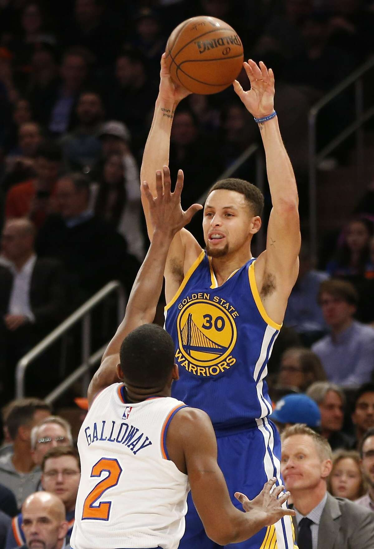Golden State Warriors guard Stephen Curry passes over New York Knicks guard Langston Galloway in the first half of an NBA basketball game at Madison Square Garden in New York, Sunday, Jan. 31, 2016.