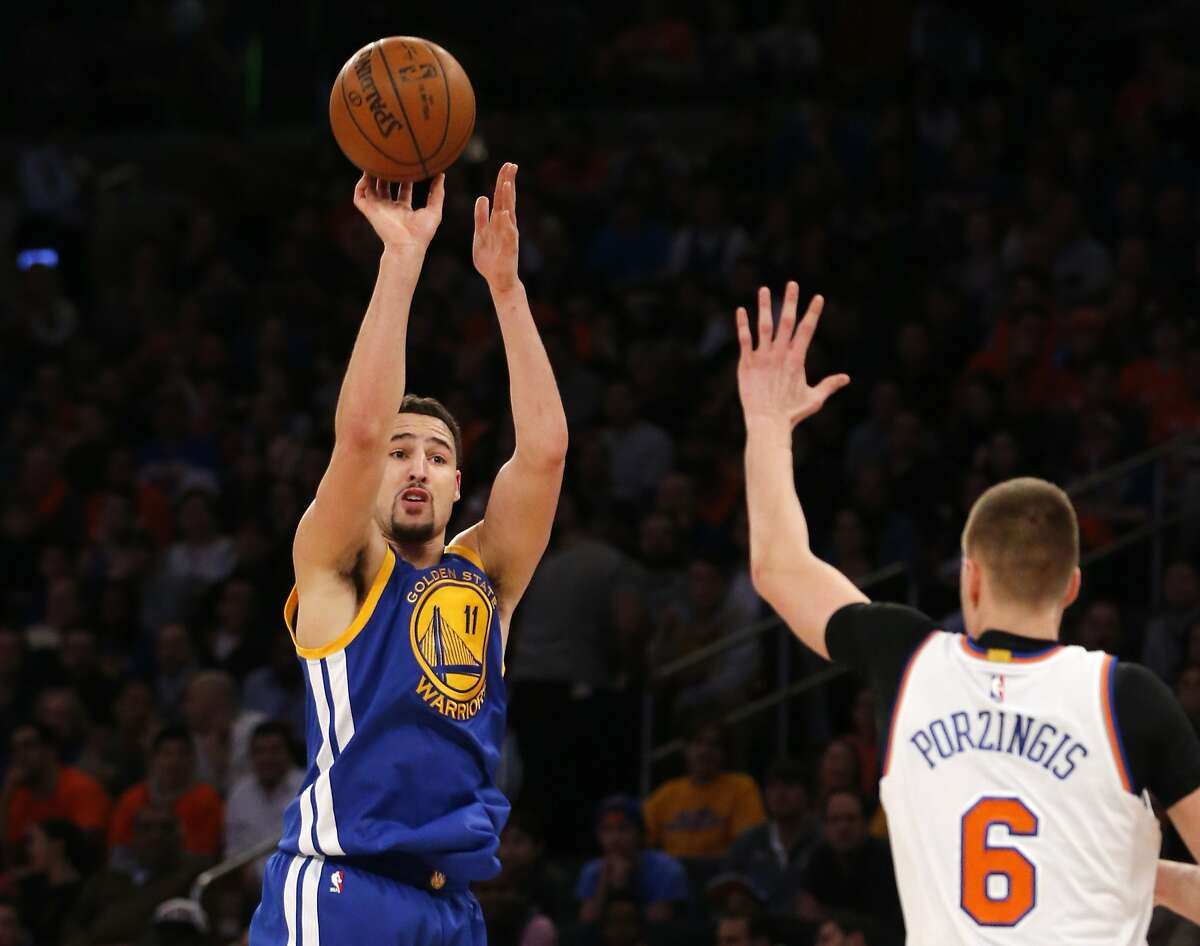 Golden State Warriors guard Klay Thompson shoots as New York Knicks forward Kristaps Porzingis defends in the first half of an NBA basketball game at Madison Square Garden in New York, Sunday, Jan. 31, 2016.