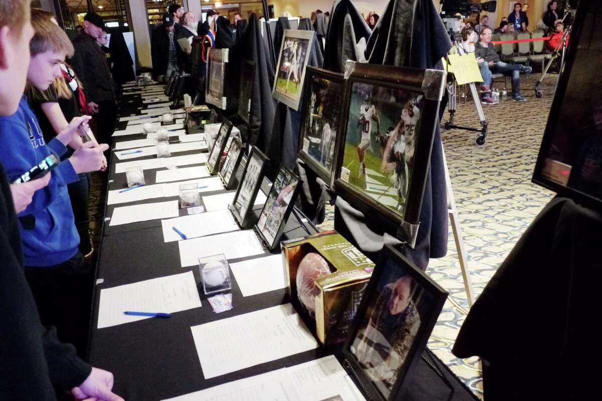 Visitors look over the different sports memorabilia for auction at the 56th Annual Center for Disability Services Telethon on Sunday, Jan. 31, 2016, in Colonie, N.Y. (Paul Buckowski / Times Union)