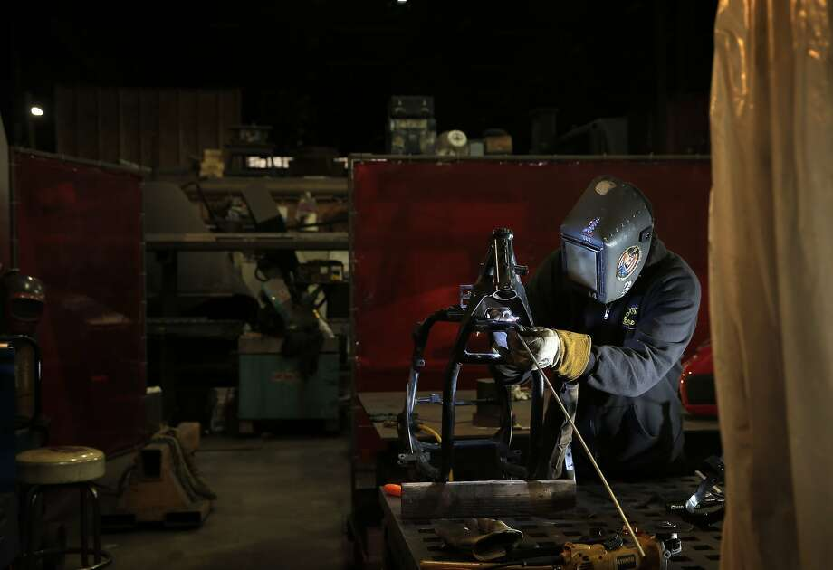 Grant Irish does some TIG welding on his motorcycle frame at American Steel in Oakland, Calif., on Sunday, January 31, 2016.  Irish is a sculpture artist facing an uncertain future at American Steel, a prominent arts warehouse that's become a coveted piece of Oakland real estate. The owner has quietly put his 12-acre property on the market for $30 million, and various would-be developers have jockeyed to buy it. Photo: Carlos Avila Gonzalez, The Chronicle