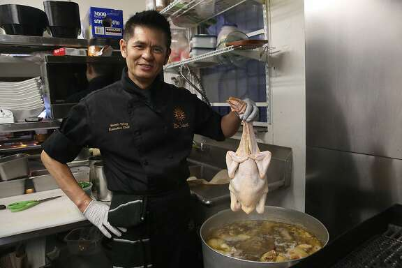 Le Soleil executive chef Dennis Wong places chicken in boiler for Hainan chicken in San Francisco, California, on Friday,  January 29, 2016.